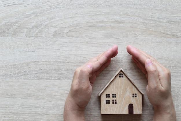 Main protégeant la maison modèle sur fond de bois