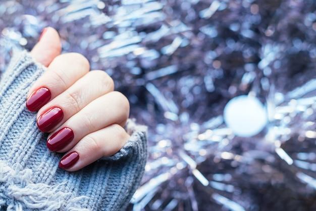 Main en pull tricoté avec des clous bordeaux sur fond de guirlande de guirlandes de noël rose pâle