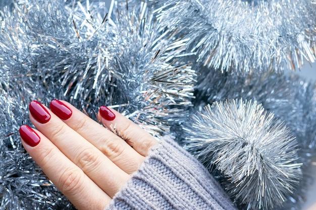 Main en pull tricoté avec des clous bordeaux