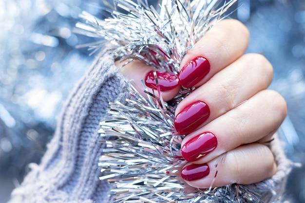Main en pull tricoté avec des ongles rouge foncé