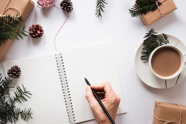 Main qui écrit sur le cahier près de boisson chaude