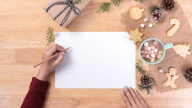Main qui écrit la carte postale de maquette pour faire la liste et le chocolat chaud avec de la guimauve, cookie sur fond en bois. hiver noël et bonne année concept.