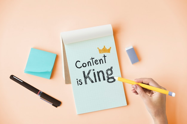 Main qui écrit le contenu est roi sur un bloc-notes