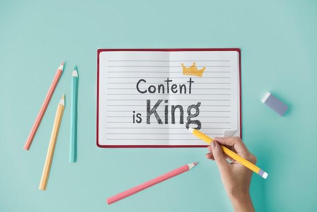 Main qui écrit le contenu est roi sur un cahier