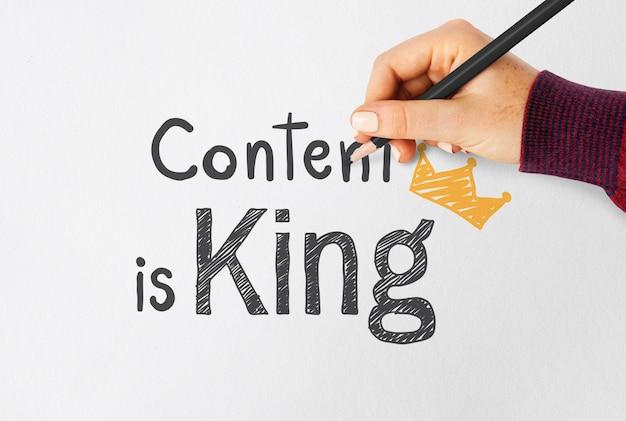 Main qui écrit le contenu est roi sur un papier
