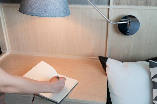 Main qui écrit dans un cahier au bureau avec lampe