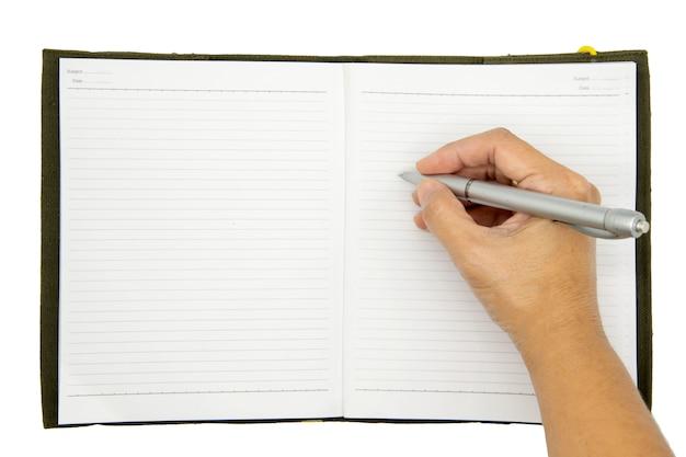 Main qui écrit dans un cahier au crayon sur une table en bois.