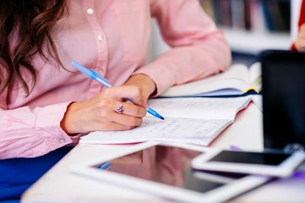 Main qui écrit dans le cahier à table