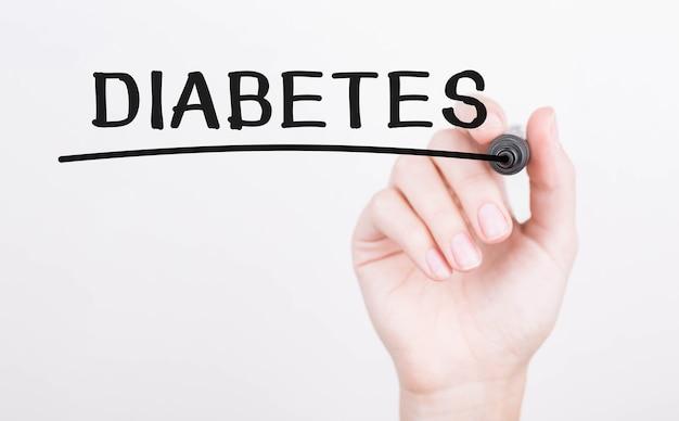 Main qui écrit le diabète avec un marqueur noir à bord transparent.