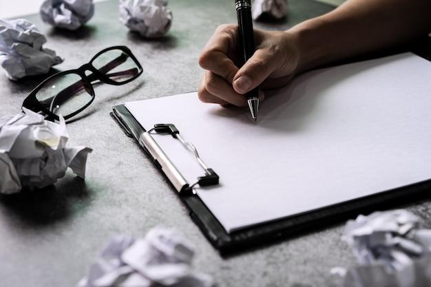 Main qui écrit sur le dossier avec des boules de papier froissé sur le bureau, concept de problèmes de créativité