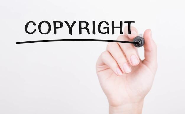 Main qui écrit le droit d'auteur avec un marqueur noir sur un chiffon transparent