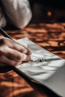 Main qui écrit sur du papier blanc avec une mine de crayon cassée