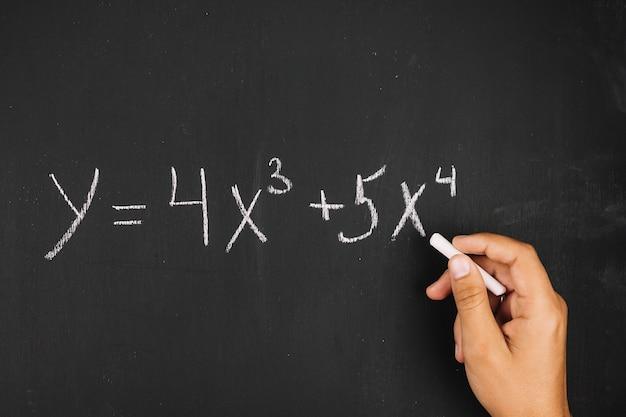 Main qui écrit l'équation mathématique