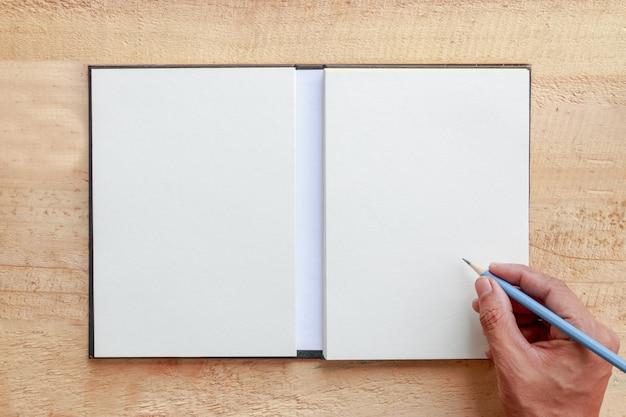 Main qui écrit sur fond de papier
