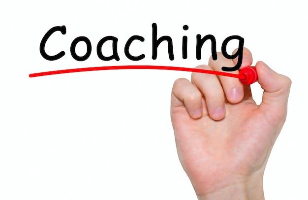 Main qui écrit inscription coaching avec marqueur, concept