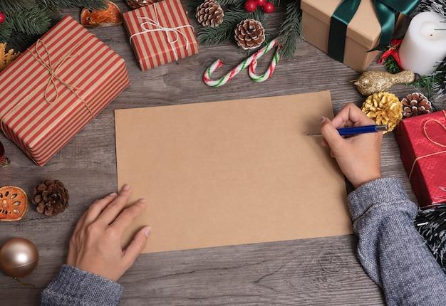 Main qui écrit la maquette de carte de voeux pour joyeux noël et heureux avec décoration de noël sur table en bois.