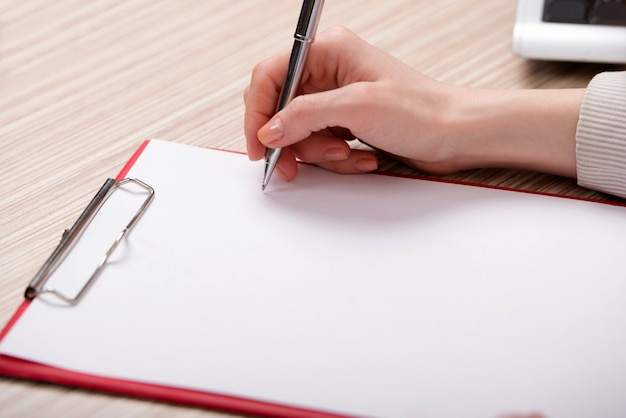 Main qui écrit un mémo au concept d'entreprise