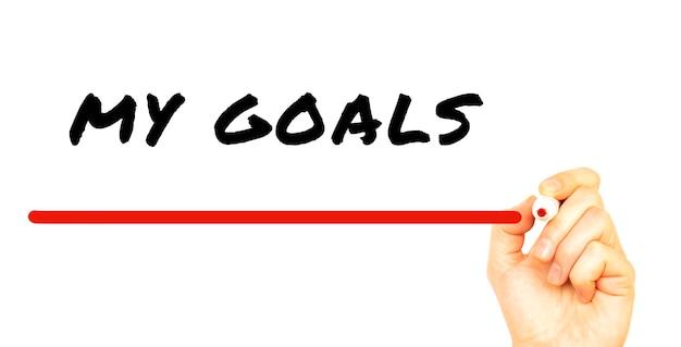 Main qui écrit mes objectifs avec un marqueur rouge. isolé sur une surface blanche