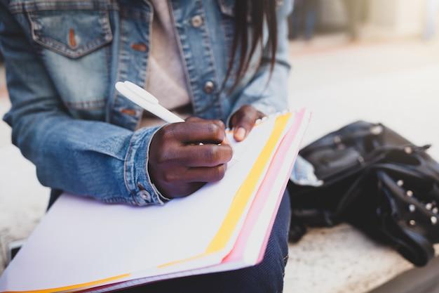 Main qui écrit des notes dans un cahier.