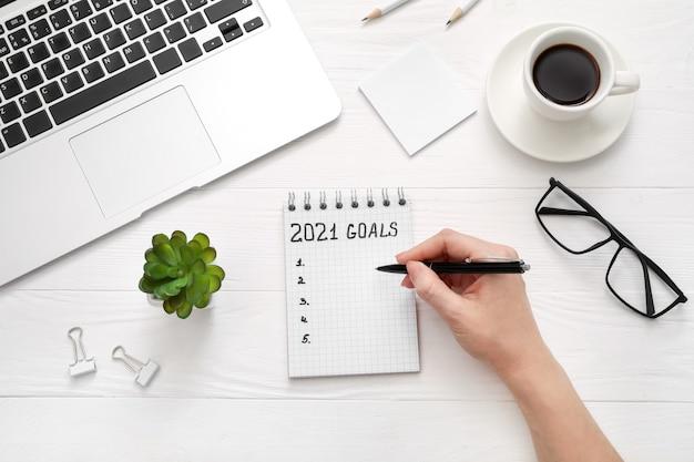 Main qui écrit des objectifs pour le nouvel an dans un nouveau cahier sur un bureau en bois blanc