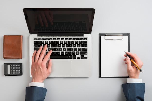Main qui écrit sur le presse-papiers et l'ordinateur portable