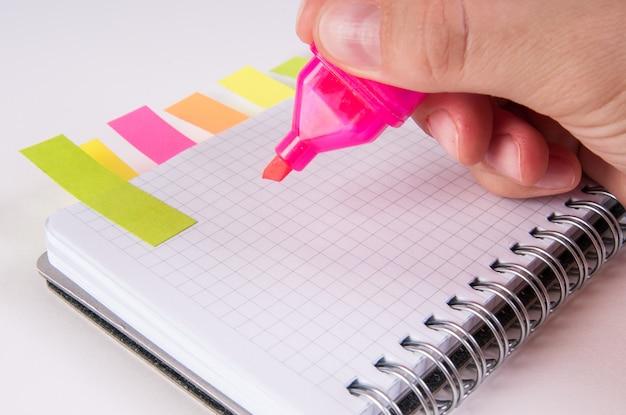 Main qui écrit en rose sur le bloc-notes vide,