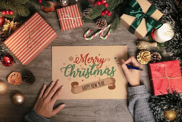 Main qui écrit le texte joyeux noël de carte de voeux avec la décoration de noël sur la table en bois.