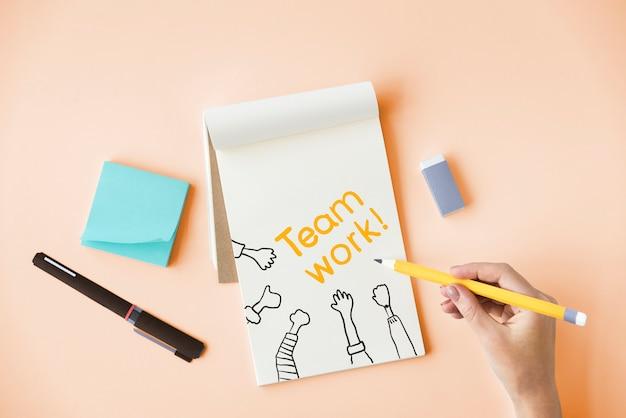 Main qui écrit le travail d'équipe sur un bloc-notes