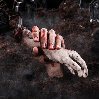 Main qui sort la terre en tenant la main morte