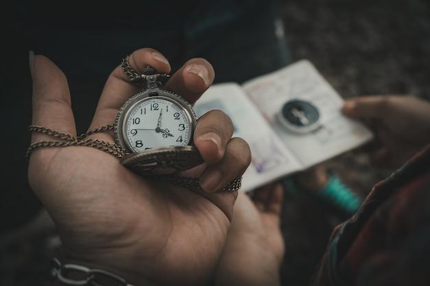 La main qui tient l'horloge et l'arrière-plan flou passe sport et boussole.
