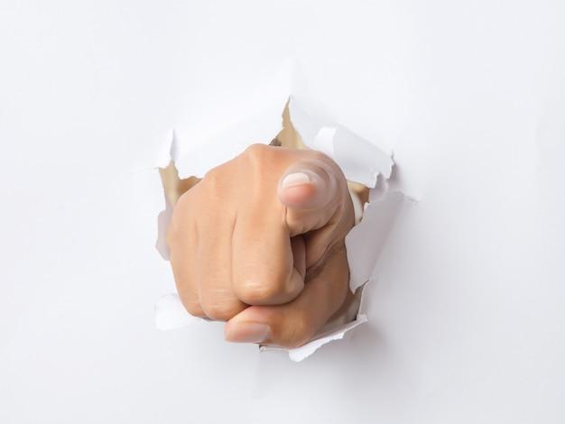 Main qui traverse le papier pointant vers vous