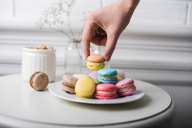 Main ramasser le macaron de plaque blanche conservée sur la table blanche