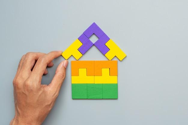 Main reliant le bloc de forme d'accueil avec des pièces de puzzle en bois coloré sur fond gris