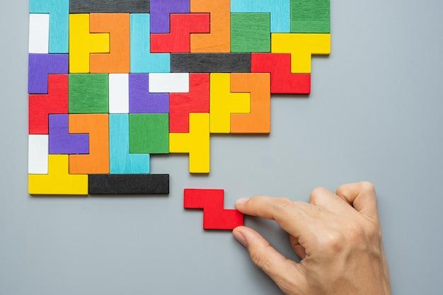 Main reliant le bloc de forme géométrique avec des pièces de puzzle en bois colorées.