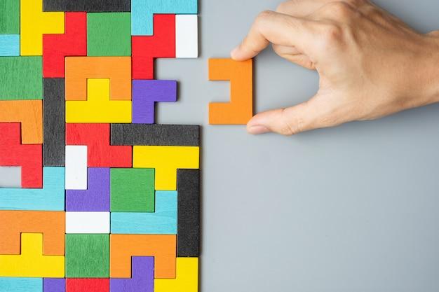 Main reliant le bloc de forme géométrique avec des pièces de puzzle en bois colorées