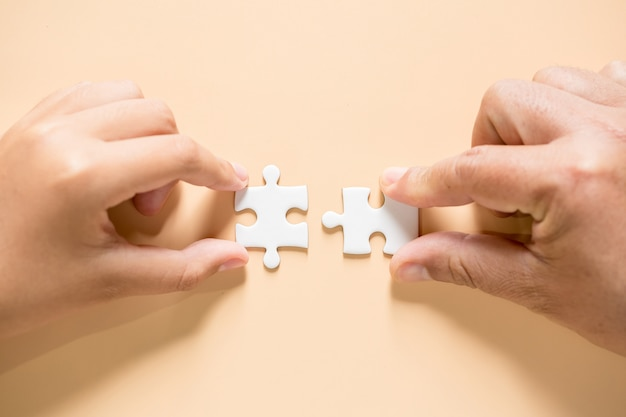 Main reliant des pièces de puzzle sur la table