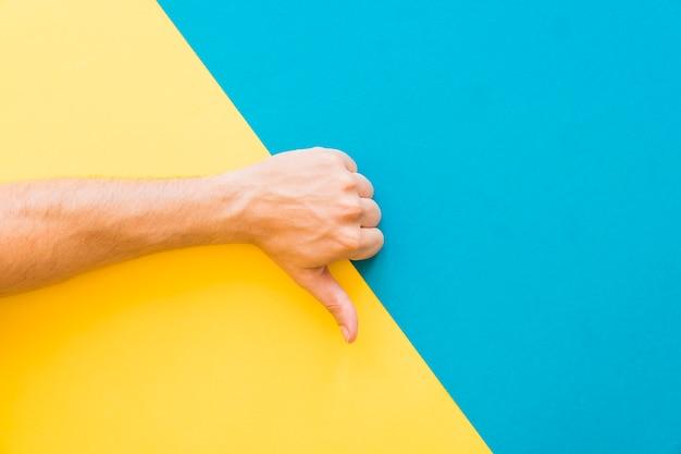 La main rend le geste des pouces vers le bas
