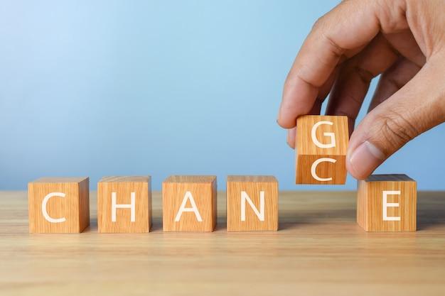Main renverser le cube en bois avec le changement de mot à la croissance ou au changement de carrière de chance