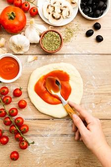 Main répandre la sauce tomate sur la pâte à pizza