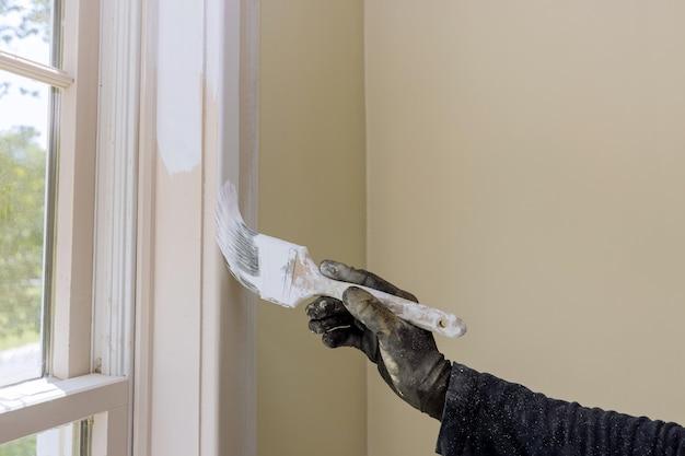 Main de réparateur peignant avec des gants dans la garniture de moulure de fenêtre de peinture