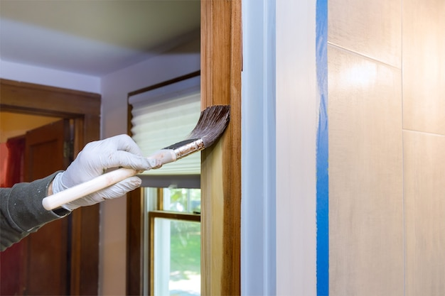 Main de réparateur peignant avec des gants dans un pinceau appliquant de la peinture vernis des portes en bois moulures avec un pinceau
