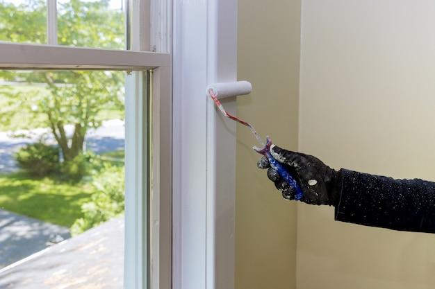 Main de réparateur peignant avec des gants un rouleau à peinture dans la garniture de moulure de fenêtre de peinture