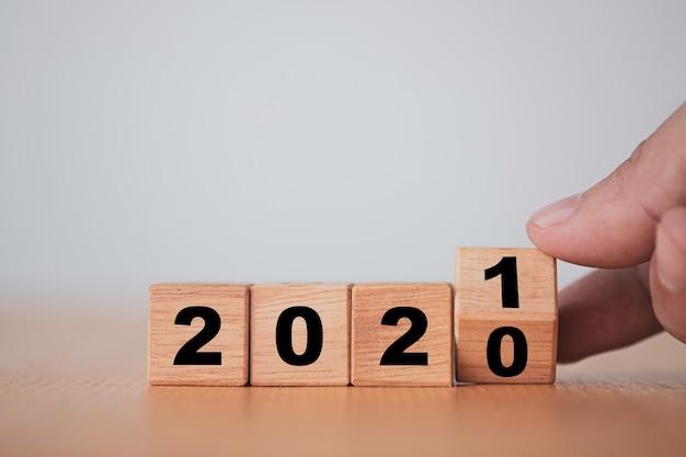 Main retournant des blocs de bois pour l'année de changement 2020 à 2021