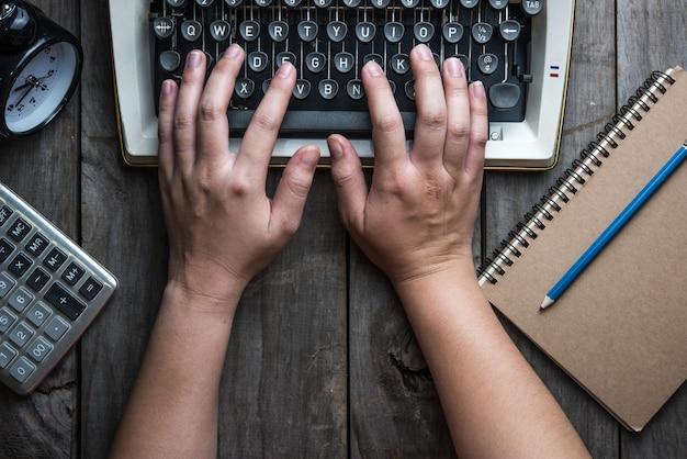 Main rétro machine à écrire sur une table en bois
