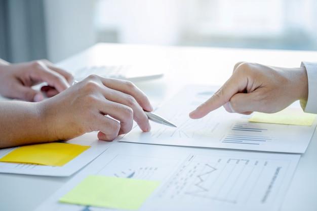 Main. réunion d'équipe de femme d'affaires et d'hommes d'affaires pour planifier des stratégies visant à augmenter les revenus de l'entreprise. ayez une analyse graphique de brainstorming et discutez du succès de la nouvelle cible.