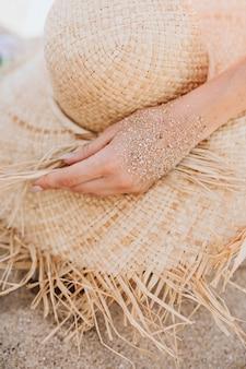 La main de sable touche un chapeau de paille