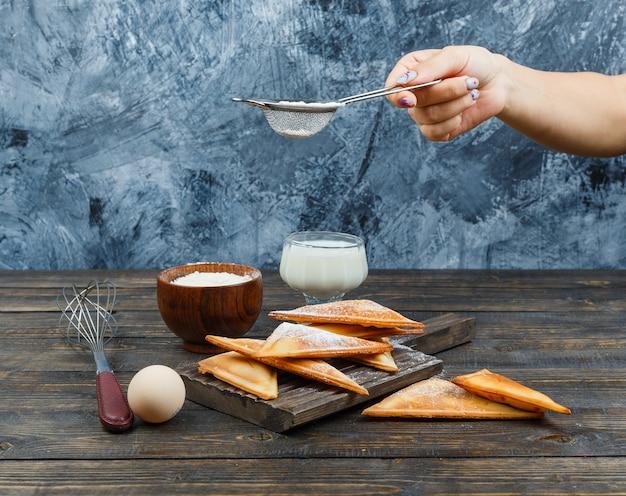 Main saupoudrer de farine sur gaufre sur planche de bois