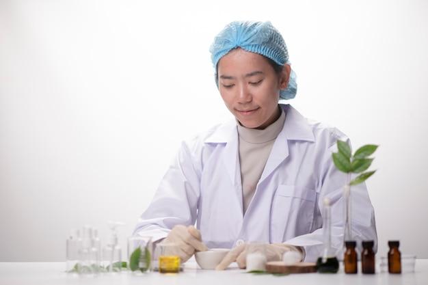 Main de scientifique sur une feuille verte dans une cuvette de verre sur le laboratoire. concept de biotechnologie.