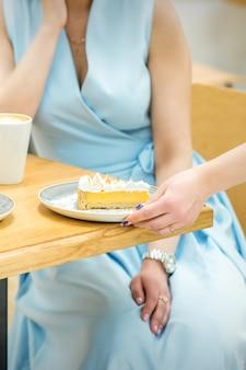 La main de la serveuse met le morceau de cupcake sur la table dans un café, la main de la femme met une petite pâtisserie ronde sur la table sur fond d'une femme en robe bleue