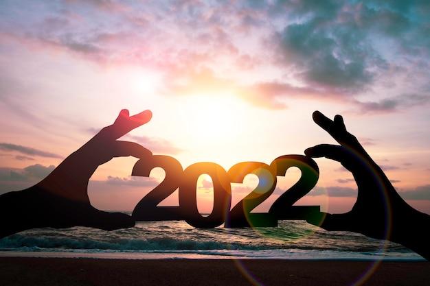 Main de silhouette tenant l'année 2022 sur le côté de la plage.